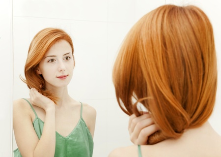 Beautiful redhead young woman with fresh skin of face in bathroom
