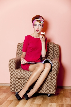 Style girl in red dress sitting in armchair with cake and magazine