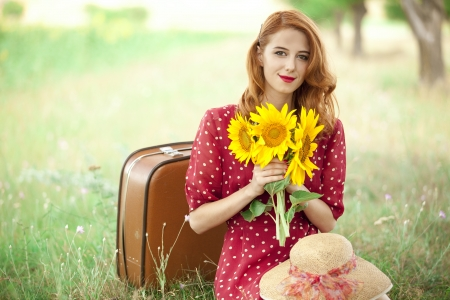 Redhead girl with sunflower at outdoor.の写真素材