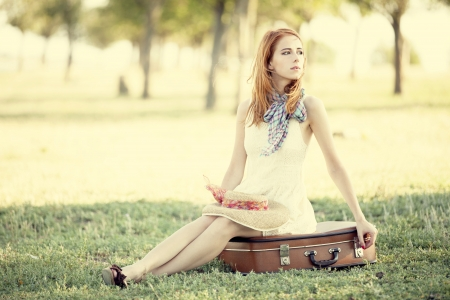 Redhead girl sitting at bag at outdoor.の写真素材