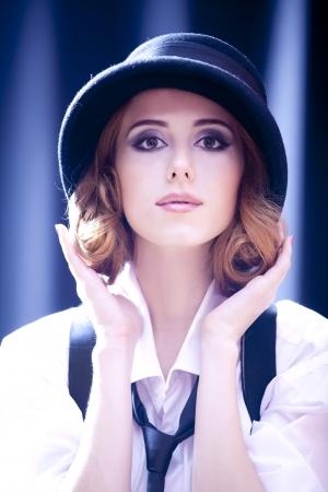 Fashion redhead girl with tie in studio.