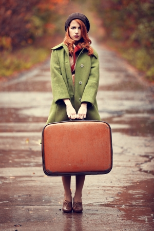 Style redhead girl with suitcase at beautiful autumn alley.の写真素材