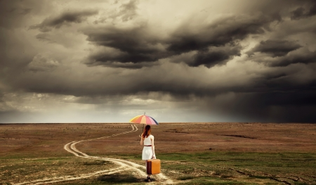 Girl with umbrella and suitcase walking by the road at countryside.