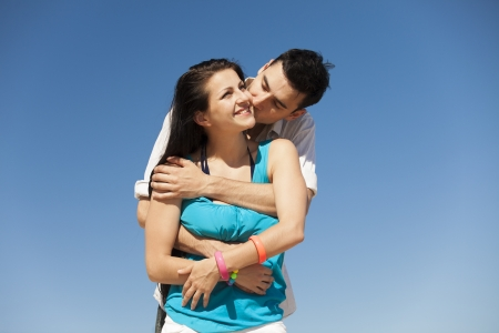 Beautiful couple kissing on blue sky background.