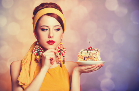 Style redhead girl with cake. Photo with bokeh at background.