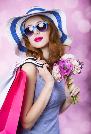 Redhead girl with shopping boxes and flowers on pink background.の写真素材