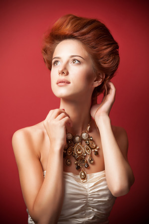 Portrait of redhead edvardian women with necklace on red .