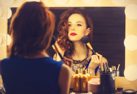 Photo for Portrait of a beautiful woman as applying makeup near a mirror. Photo in retro color style. - Royalty Free Image