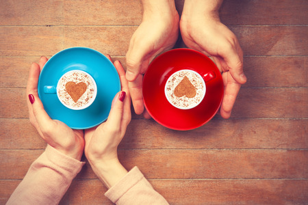 Photo pour Women and man holding cups of coffee with heart shape symbol on a wooden background - image libre de droit