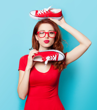 Surprised redhead girl in red dress with gumshoes on blue background.の写真素材