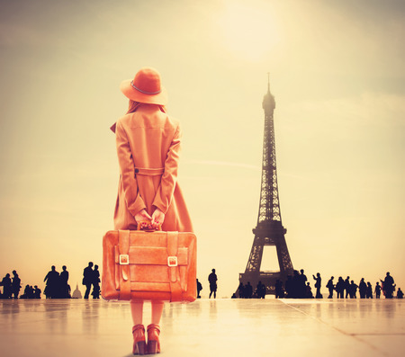 Redhead girl with suitcase on Eiffel tower backgroundの写真素材