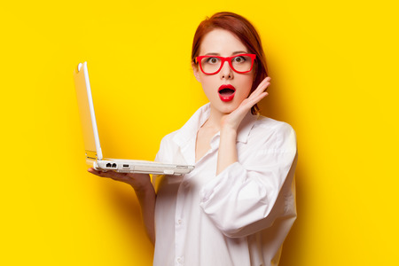 Surprised redhead girl in white shirt with computer on yelllow background.