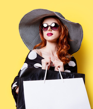 Foto de Redhead girl in black dress and hat with shopping bags on yellow background - Imagen libre de derechos