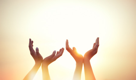 Photo for four hands on sunset background. - Royalty Free Image