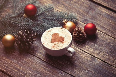 Photo pour Cup of coffee and christmas toys on wooden table. - image libre de droit