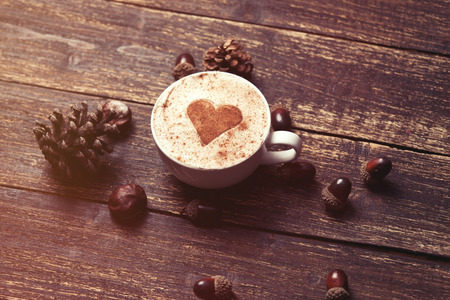 Cup of coffee with heart shape and pine cone with acorn on wooden background