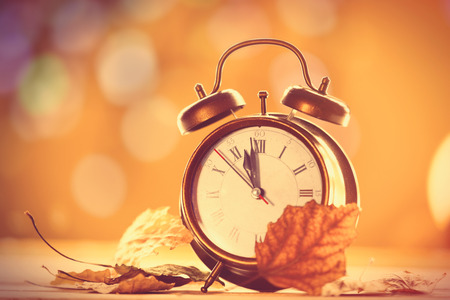 Vintage alalrm clock on yellow background with bokeh