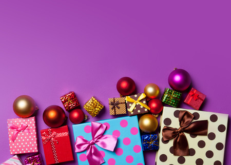 Christmas baubles and gifts on violet background