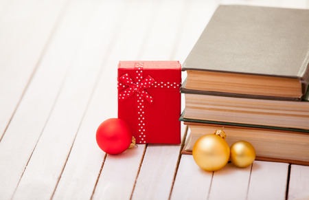 Books with christmas gifts on white table