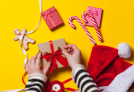 Female hands are wrapping a christmas gift on yellow background