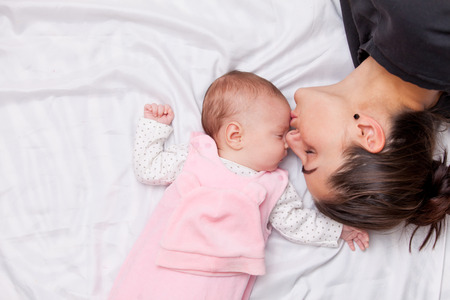 Photo pour Mother and little baby in the bed - image libre de droit