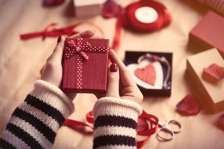 Foto de Woman preparing gift for wrapping for Valentine's Day - Imagen libre de derechos