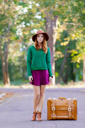 Young redhead woman with suitcase at autumn season park.の写真素材