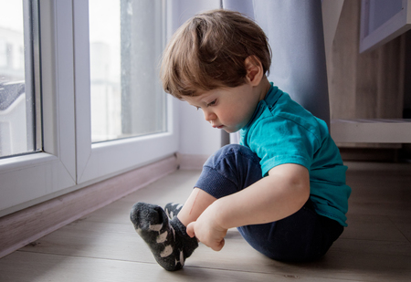 Photo pour little toddler boy sitting on floor near window and looking at foots - image libre de droit