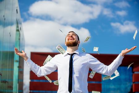 Photo pour Young businessman with falling cash money at city outdoor. - image libre de droit