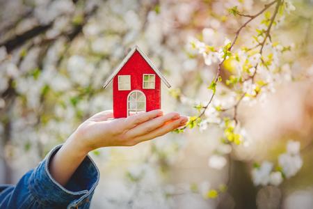 Photo pour Female hand holding red little house near flowering tree. Spring season - image libre de droit