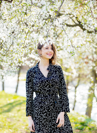 Photo pour Young girl in dark dress stay near a flowering tree in the park. Spring season - image libre de droit