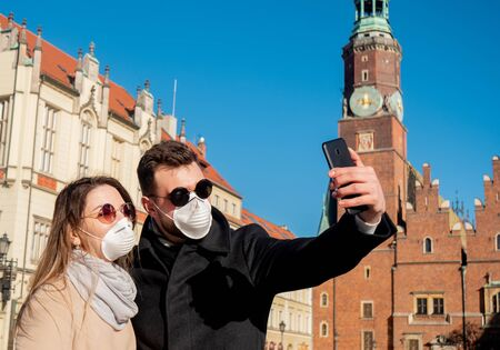 Photo pour young masked couple takes a selfie in the background of a landmark in Wroclaw, Poland - image libre de droit