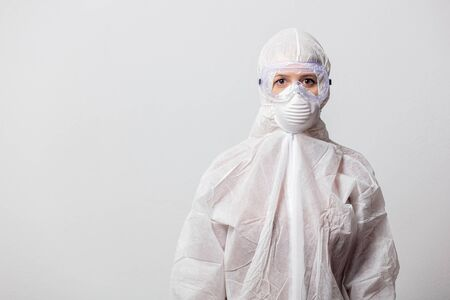 Photo pour young doctor in protection suit and glasses with mask on white background - image libre de droit