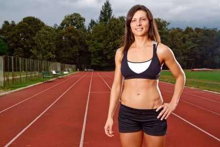 Athletic woman with a big smile on track