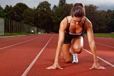 Photo pour Athletic woman in start position on track - image libre de droit