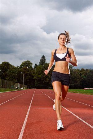 Photo pour Athletic woman running on track  - image libre de droit