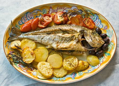 Fresh fish cooked in owen with potatoes, tomatoes and olives.