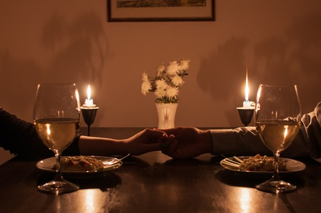 Foto de Loving couple holding hands during romantic dinner - Imagen libre de derechos