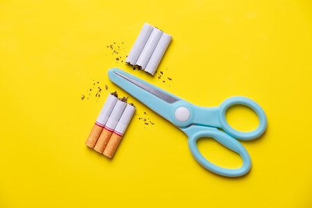 Photo pour Blue scissors cut cigarette and tobacco on yellow background pastel tone. quitting smoking for teenage smoker concept. - image libre de droit