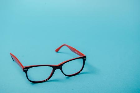 Photo pour pair of red plastic-rimmed eyeglasses on a blue background - image libre de droit