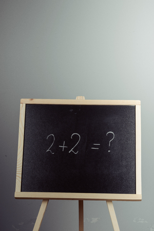 Math exercise written on the chalkboard. Gray background