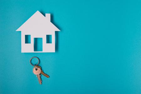 Foto de Silver key with house figure on blue background. Top view. - Imagen libre de derechos