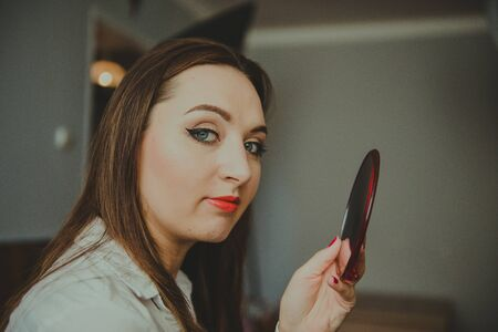 woman with strong makeup holds a mirror in her hand.