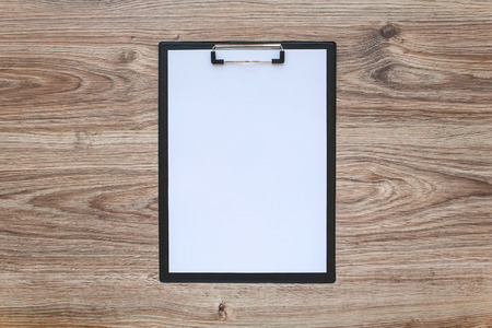 Blank white paper sheet in a clipboard on wooden table. Template.