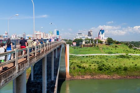 CIUDAD DEL ESTE, PARAGUAY - FEB 7, 2015: People and vehicles cross Friendship Bridge between Brazil and Paraguay, Ciudad del Este city in the background.