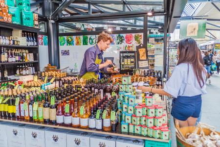 COPENHAGEN, DENMARK - AUGUST 28, 2016: People shop at a stall inTorvehallerne indoor food market in the centre of Copenhagen.