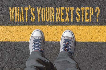 Photo pour What`s your next step?, print with sneakers on asphalt road, top view. - image libre de droit
