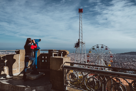 Woman looking at the city of Barcelona from Tibidabo, using a coin operated pair of binoculars. 2019