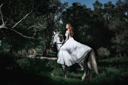 Foto de Beautiful and stunning bride, riding a horse in the nature, on her wedding day - Imagen libre de derechos