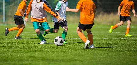 Foto de Football soccer match for children. kids playing soccer game tournament. physical education classes at school. - Imagen libre de derechos